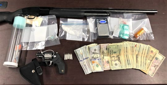 Weapons, drugs and cash recovered during a raid executed by the Fairfield-Athens-Hocking Major Crimes Unit Thursday, Jan. 9. Three people were arrested in connection to two search warrants after citizen comments reported suspected drug activity at two Lancaster homes.