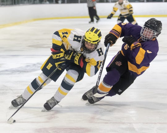 Hartland's Seth Ferguson skates around Jacob Jansen to score a goal in a 9-4 victory over Warren DeLaSalle on Wednesday, Jan. 8, 2020.