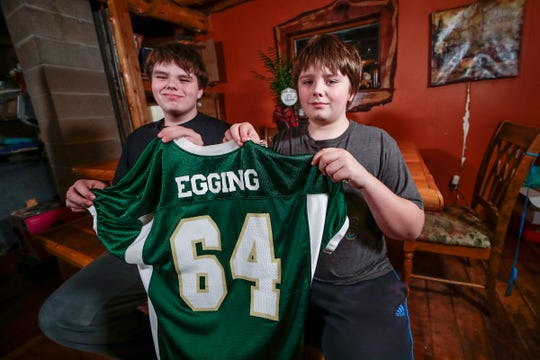 Andy, left, and Henry Egging hold their brother Sam's junior varsity football jersey. Sam, who wore No. 64 on the JV team before switching to No. 66, died Dec. 19.
