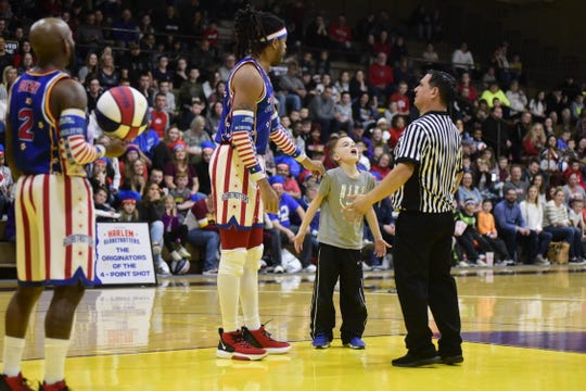 Dylan Wagner, 9, of Mansfield, helps the Harlem Globetrotters argue a call with the referee during Wednesday's game at Lexington High School.