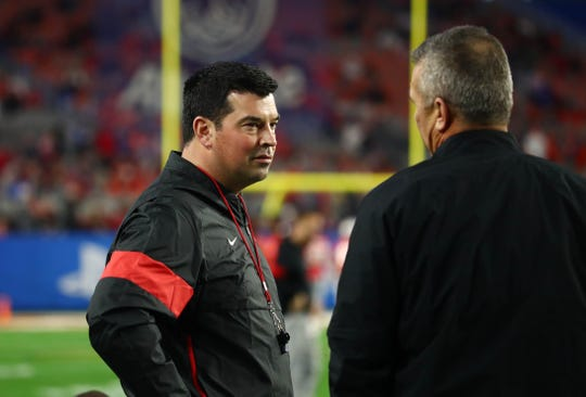 Ohio State's Ryan Day, 13-1 in his first full season as head coach, talks with predecessor Urban Meyer before the Fiesta Bowl.