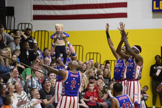 A young fan is held high above the crowd by the Harlem Globetrotters during Wednesday's game at Lexington High School.