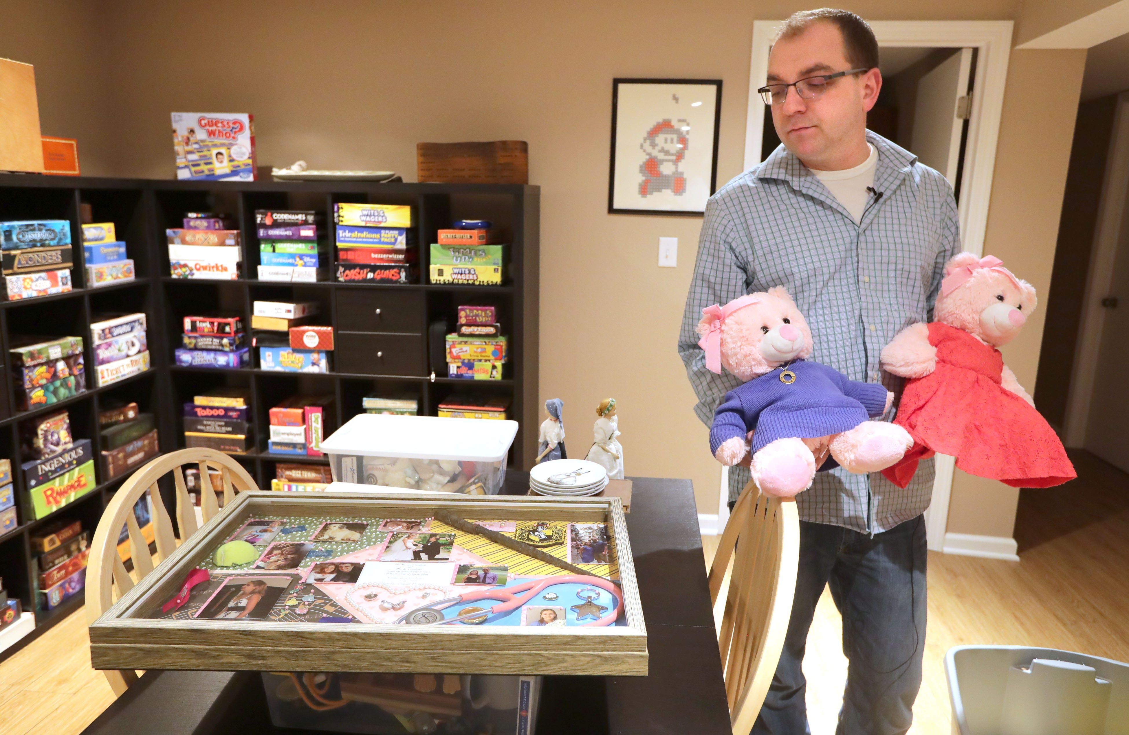 Nick Beaudin, husband of Carlie Beaudin, the Froedtert nurse practitioner who was beaten to death in Froedtert Hospital'sparking garage, holds a couple of teddy bears with outfits made from the clothes of his wife as he looks at a framed collection of photos and memorabilia of Carlie. Nick had several of Carlie outfits made to fit the teddy bears he called Carlie Bears and gave them to family and friends. He's pictured in his home in Greendale on Wednesday, Jan. 8, 2020.   Photo by Mike De Sisti / Milwaukee Journal Sentinel