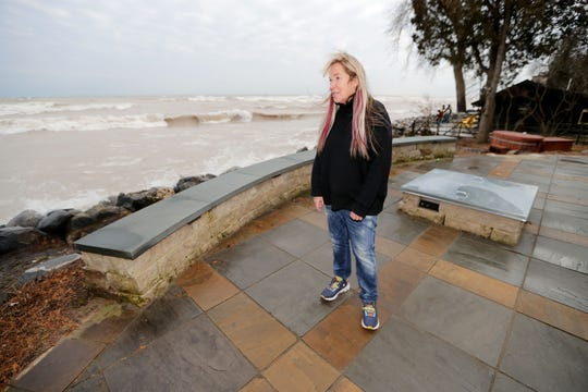 Robin Shellow watches as waves from Lake Michigan wash over boulders in the backyard of her home in Belgium on Thursday.