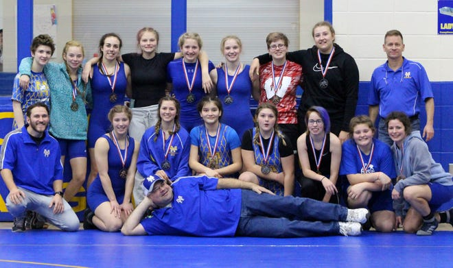 The Lady Bomber wrestling team and coaches pose for a photograph after the recent Bomber Battle tournament at The Hangar.