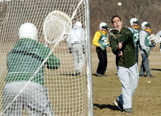 Mark Grilo and his wife, Amy Richter, launched the Morris Knolls lacrosse programs in 2006. Grilo warms up one of his goalies at the start of practice during the inaugural season.
