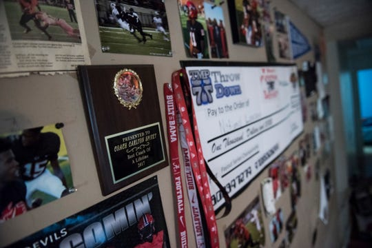 Carlton Spivey hangs pictures and other memorabilia from his son and other players carers at his home in Phenix City, Ala., on Tuesday, Jan. 7, 2020.