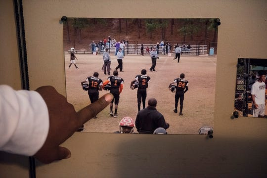 Carlton Spivey points out a picture of his sons and Clemson's Justyn Ross from early in their football careers at his home in Phenix City, Ala., on Tuesday, Jan. 7, 2020.