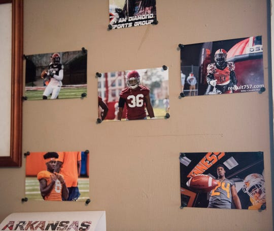 Carlton Spivey hangs pictures of his sons and former players including Alabama's Markail Benton and Clemson's Justyn Ross at his home in Phenix City, Ala., on Tuesday, Jan. 7, 2020.