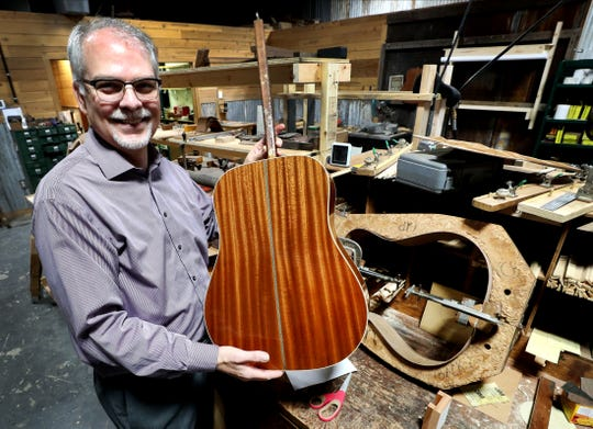 David Mathis, the new owner of Gallagher Guitar Co., shows off a guitar that his company is refinishing in the new downtown Murfreesboro location on Tuesday, Jan. 7, 2020.