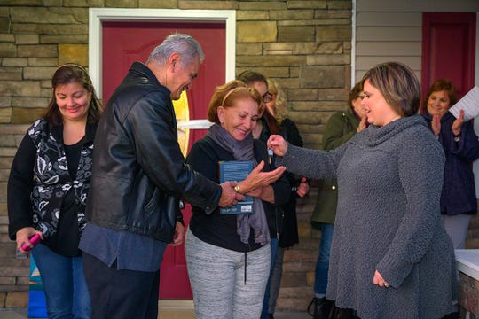 Jackie Victory, right, director of MTSU Student Organizations and Service, hands Carlos Rivero-Odermatt and Rafela Aldas the keys to the new home on East Castle Street in Murfreesboro Wednesday. MTSU students and other volunteers helped build the home.