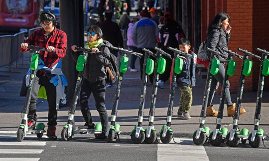 Scooters line the corner of 4th and Broadway in downtown Nashville.