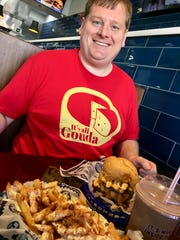 Nashville food blogger Josh Miller poses with the one-pound cheeseburger, milkshake and loaded queso fries he wiped out in 18 minutes as part of Hoss' Loaded Burgers Jaw Dropper Challenge Jan. 8, 2020, in Nolensville, Tenn.