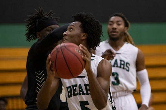 Palmetto Ridge's Malique Dieudonne (5) maneuvers under the basket as teammate Kamonte Grimes (3) comes in for backup during their game against Golden Gate, Wednesday, Jan. 8, 2020, at Palmetto Ridge High School.