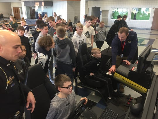 Students line up Jan. 9 in the Granville Middle and High schools' cafeteria to try a distracted driving simulator.