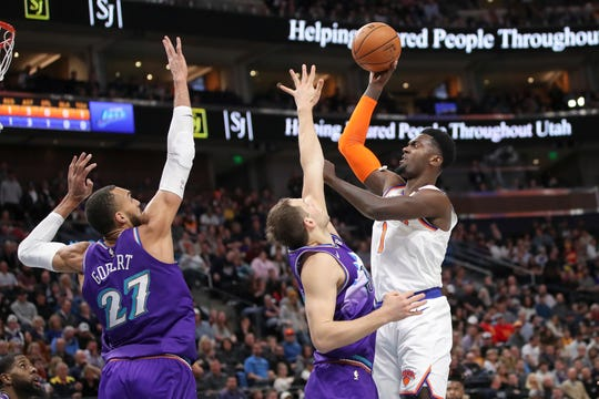 New York Knicks forward Bobby Portis (1) shoots over the arms of Utah Jazz forward Bojan Bogdanovic (44) and Utah Jazz center Rudy Gobert (27) during the first quarter of an NBA basketball game, Wednesday, Jan. 8, 2020, in Salt Lake City.