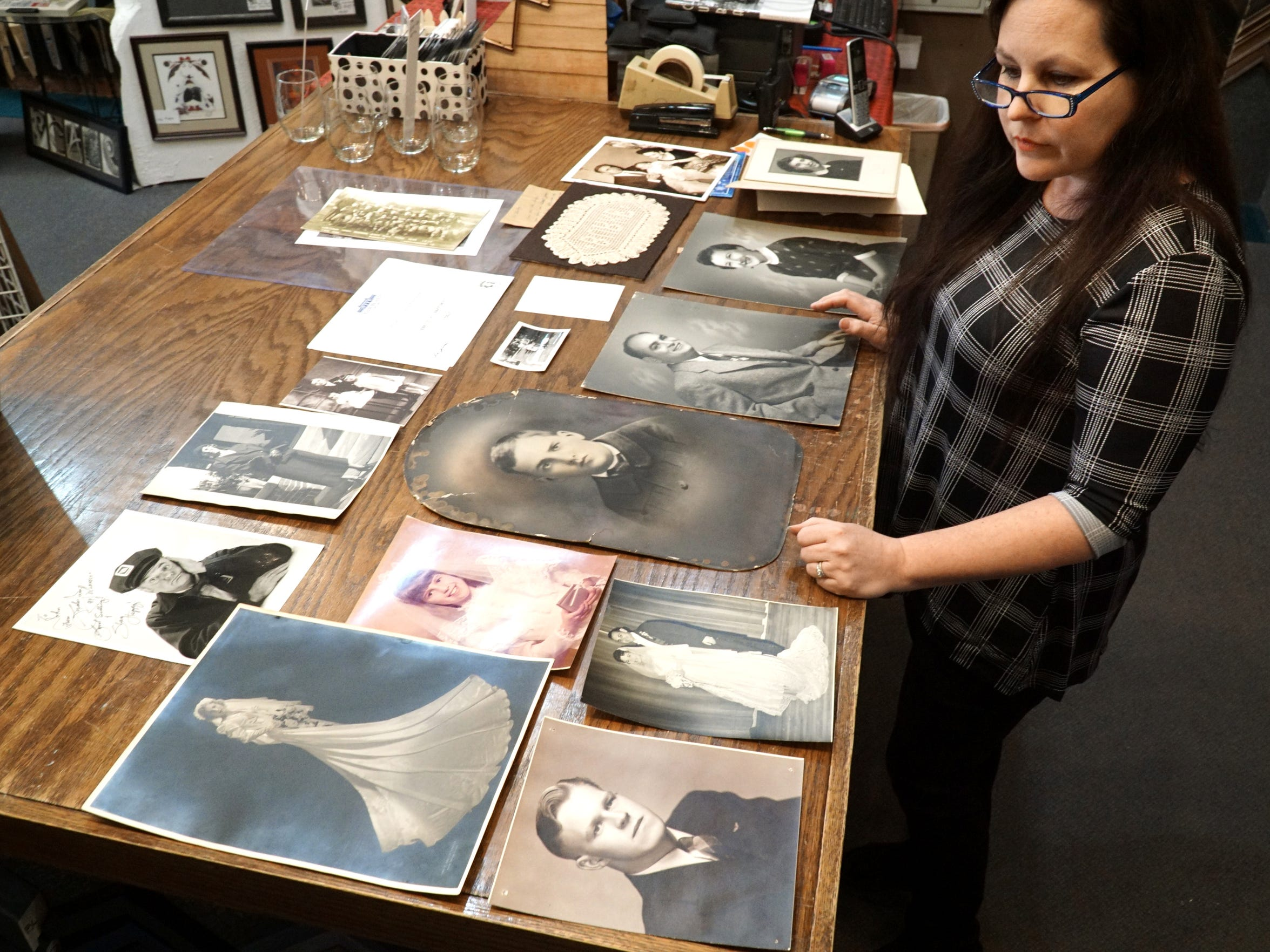 Cindy Eckley places some of the many portrait photos left by customers over the decades at Plymouth's Frame Works on Penniman Ave. Through Facebook postings she's attempting to reunite the images with their owners - or decendants of their owners.