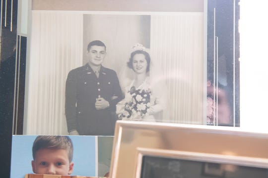 A portrait of David and Marie Houck on their wedding day is displayed along with other family photos inside David's room at The Village at Utz Terrace. The Houcks were married for almost 73 years.
