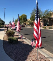 On the day after Dustin Harrison, of Gilbert, was killed in a terrorist attack in Kenya, neighbors put up close to 200 American flags through Stratland Estates where the family lived.