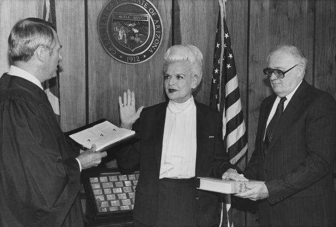 Arizona Supreme Court Justice Frank Gordon Jr. swears in Gov. Rose Mofford with  William A. Holshan in 1988.