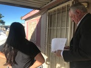 Linn Carrasco and Ron Bellus, of the Maricopa County Treasurer's Office, wait at the door of a mobile home to talk to the resident about late taxes that are due.