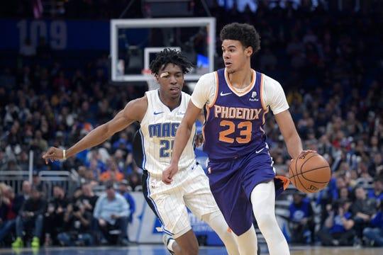 Phoenix Suns forward Cameron Johnson (23) drives to the basket in front of Orlando Magic forward Wes Iwundu (25) during the second half of an NBA basketball game Wednesday, Dec. 4, 2019, in Orlando, Fla. (AP Photo/Phelan M. Ebenhack)