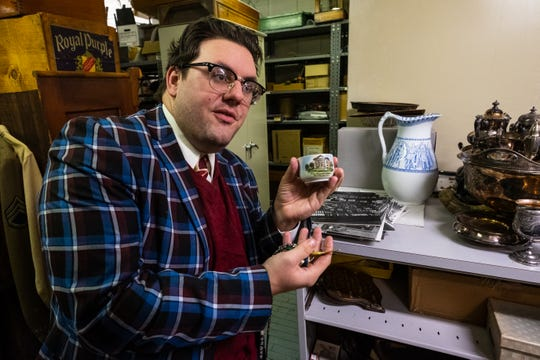 Port Huron Museums Community Engagement Manager Andrew Kercher holds a teacup with a picture of the Maccabees building from 1968 on Wednesday, Jan. 8, 2020, in the archives of the Port Huron Museum's Carnegie Center.
