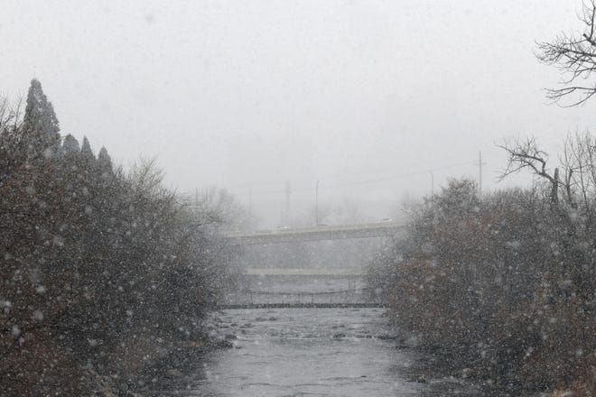 A brief period of snowfall clouds the view of downtown and the Wells Avenue bridge from the Sutro Street bridge over the Truckee River on Jan. 9, 2020.