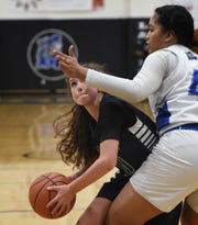 Damonte's Alyssa Barnard look to shoot against McQueen's Alisi Peaua during Tuesday night's game at McQueen.