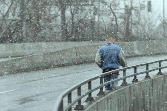 A man walks across the Sutro Street bridge on Jan. 9, 2020 as snow falls on Reno.