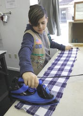 Quest Club member Aaron Jimenez irons fabric before it's made into a joey sack for Australian wildlife that survived the Australian fires. Aaron was part of a group who started the sewing project at the Redding Fashion Alliance on Thursday, Jan. 9, 2020.