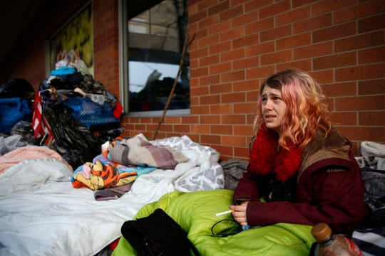 Virginia Perkins, 25, sits outside the Ross store after moving from the sidewalk outside the former Nordstrom before crews come in to clean the area in downtown Salem on Jan. 9, 2020. People experiencing homelessness have been staying outside the former Nordstrom and the Rite Aid downtown for about two weeks.