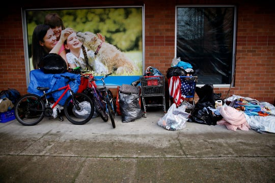 People moved belongings to the outside of the Ross store in downtown Salem after crews cleaned the area outside the empty Nordstrom store in January.