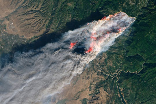 This November 2018 image shows flames and smoke from the Camp Fire that erupted 90 miles north of Sacramento, Calif.