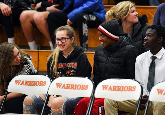 Mhiretab Tsegaye, center right, talks with friends between quarters of the Washington High School basketball game against Huron on Thursday, Jan. 2, in Sioux Falls.