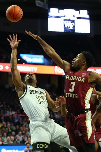Jan 8, 2020; Winston-Salem, North Carolina, USA; Wake Forest Demon Deacons guard Andrien White (13) shoots the ball against Florida State Seminoles guard Trent Forrest (3) during the first half at Lawrence Joel Veterans Memorial Coliseum. Mandatory Credit: Jeremy Brevard-USA TODAY Sports