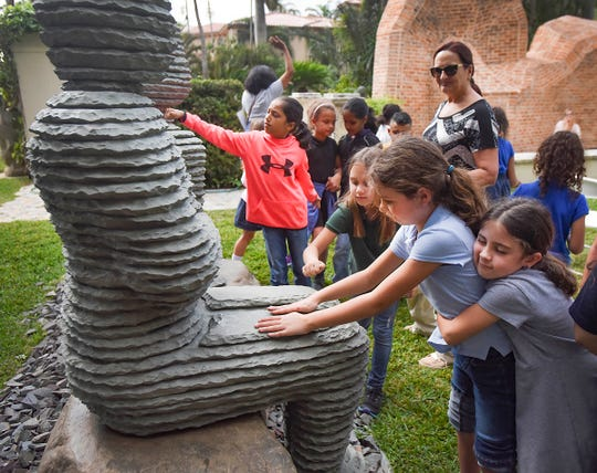 South Olive Elementary School second-grader Hana Zabovnik gets a hug from her best friend and classmate, Grace Zambrano, as she feels a sculpture by Boaz Vaadia at the Ann Norton Sculpture Gardens in West Palm Beach. Children from four schools participated in Garden Day.