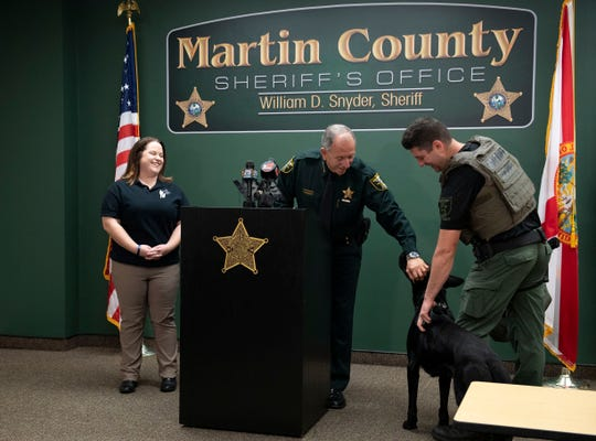 """K-9 Strong co-founder Jenna Radtke (left) and Martin County Sheriff William Snyder (center) present Corporal Ron Manganiello and K-9 Maverick with a protective vest for the German shepherd during a news conference Thursday, Jan. 9, 2020, at the sheriff's office in Stuart. K-9 Strong vested three new Martin County K-9 officers and four other K-9s with the custom fit bullet- and knife-proof vests. """"I think the people of Martin County will be happy to know these dogs are protected,"""" Snyder said."""