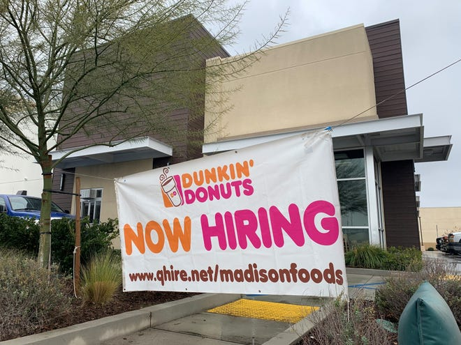 """A """"Now Hiring"""" banner hangs in front of the future Dunkin' Donuts at the corner of Mooney Boulevard and Walnut Avenue in Visalia. The coffee and donut shop is set to open early this year."""