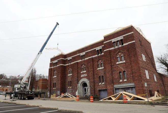 A roofing crew lifts a truss onto the roof 814 Elberon Avenue, which in the past has housed an Ohio National Guard armory, art studios and was once slated to become a homeless shelter. It has been vacant for several years.