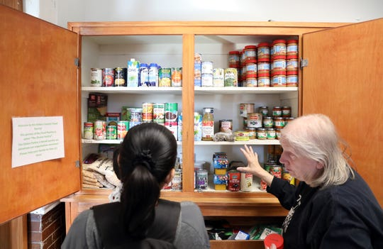 Volunteer Kathy Hartman helps Indubama Herath choose food at the Athens County Food Pantry in the Athens County Job and Family Services building near Chauncy on Thursday. The pantry has received more than $500,000 in donations since it was mentioned by LSU quarterback and Athens High School standout Joe Burrow during his Heisman Trophy acceptance speech.