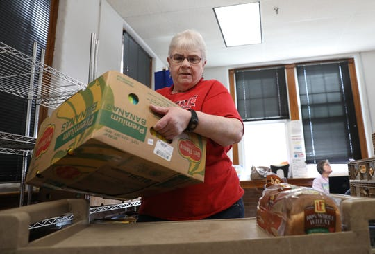 Volunteer Brenda Nelson loads a cart with a box of food at the Athens County Food Pantry in the Job and Family Services building near Chauncey on Thursday. Athens County Food Pantry President Karin Bright said the pantry board met with attorneys to discuss the future of what would be done with the surplus of funds received after Joe Burrow's Heisman acceptance speech. There are multiple options, from sharing with other organizations to creatingendowments. They hope to come up with a final solution soon.