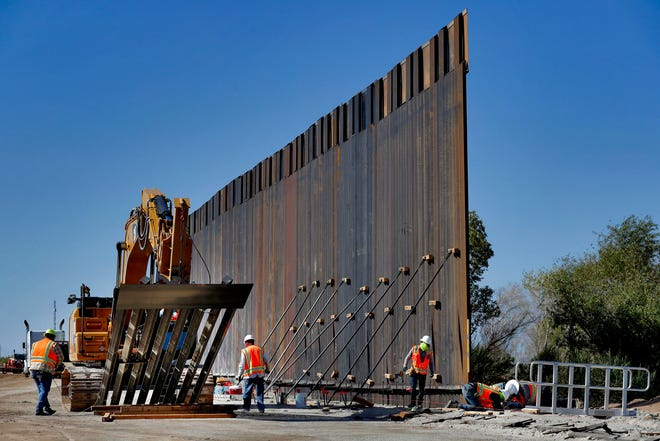 In this Sept. 10, 2019, file photo, government contractors erect a section of Pentagon-funded border wall along the Colorado River in Yuma, Ariz.