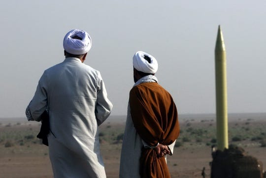 Iranian clerics look at a ballistic missile  during a military exercise at an undisclosed location in Iran, on June 28,  2011.