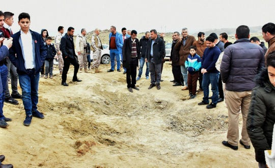 Iraqi Kurds inspect a crater caused by a reportedly Iranian missile initially fired at Iraqi bases housing U.S. and other U.S.-led coalition troops, in the Iraqi Kurdish town of Bardarash on Jan. 8, 2020.  The missiles targeted the sprawling Ain al-Asad airbase in western Iraq and a base in Arbil, both housing American and other foreign troops deployed as part of a U.S.-led coalition fighting the remnants of the Islamic State group.