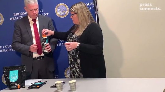Broome County Executive Jason Garnar and Marissa Knapp of the Broome County Health Department show how to dispose of medication in Deterra bags.