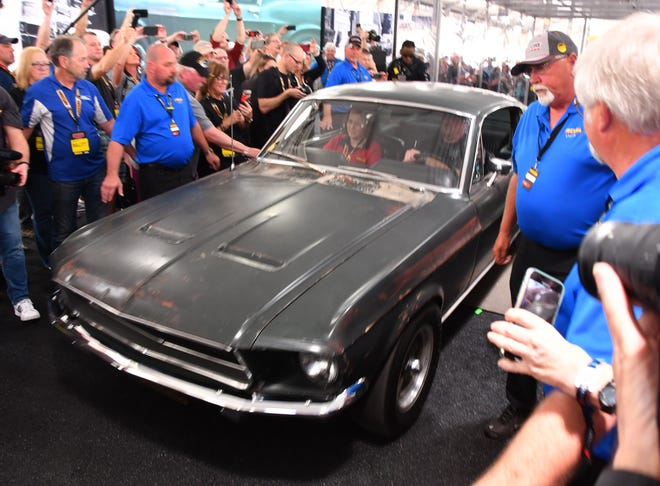 "The original 1968 fastback ""Bullitt"" Mustang on its way from the display case to the auction. The classic muscle car sold for $3.4 million at the Mecum Auction in Kissimmee, Florida, on Friday."