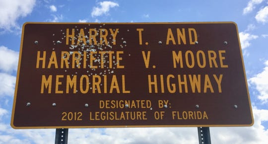 A sign designating Highway 46 as the Harry T. and Harriette V. Moore Memorial Highway at the Brevard County and Volusia County lines has been defaced by what appears to be gunshots.