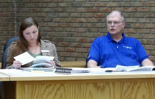 Bucyrus City Council member Bruce Truka, right,  describes the dumpsters and other items he saw in City Lot 3 while Candace Yocum looks at his photos of the lot.