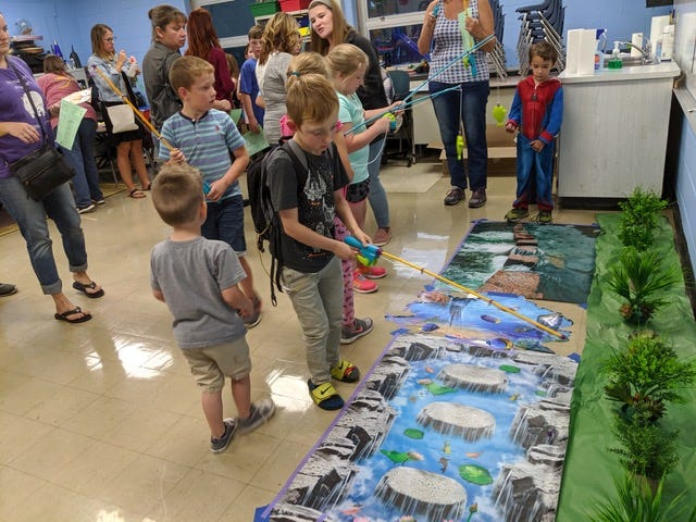 Clermont Northeastern students play a fishing-type game at the school's fall curriculum night.